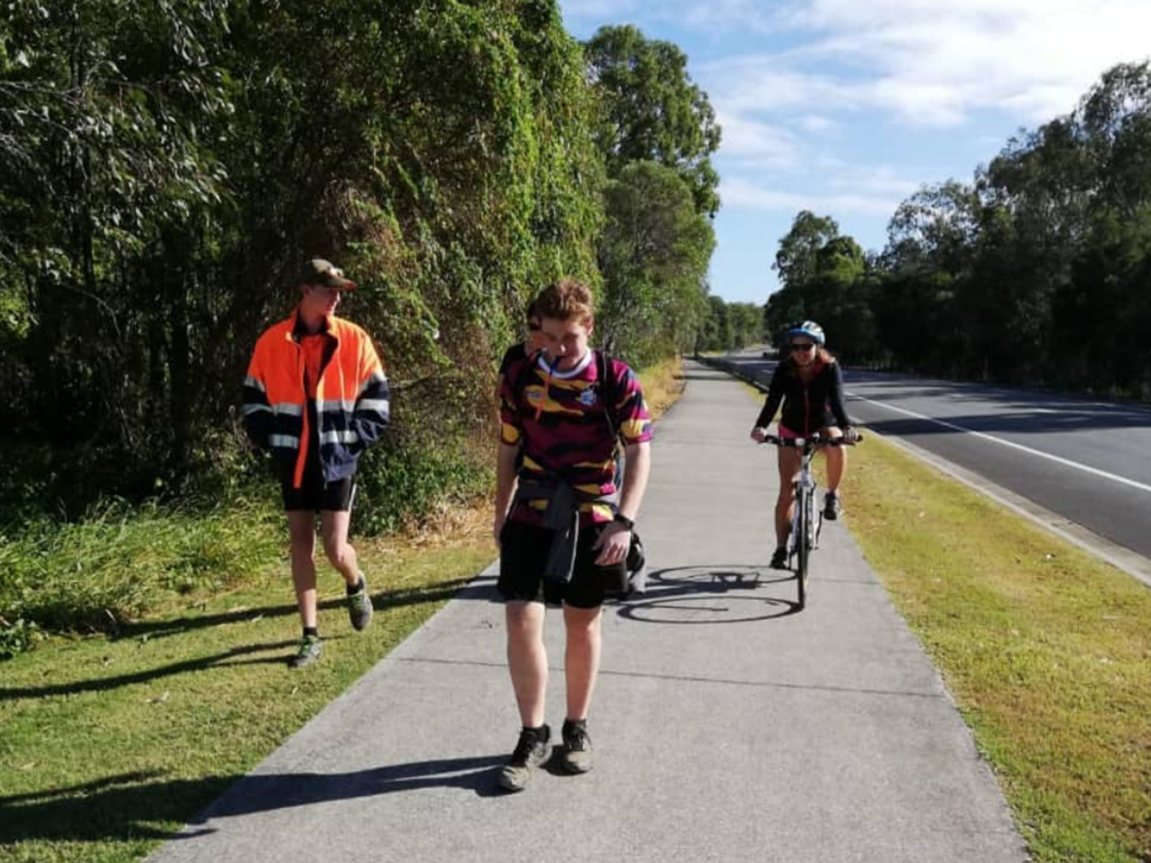 Sam Barham walking with his friend and teacher on a bike during the Kokoda Virtual Challenge