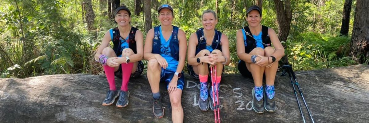 Four ladies rest on a log in the Australian bush while completing the Kokoda Virtual Challenge