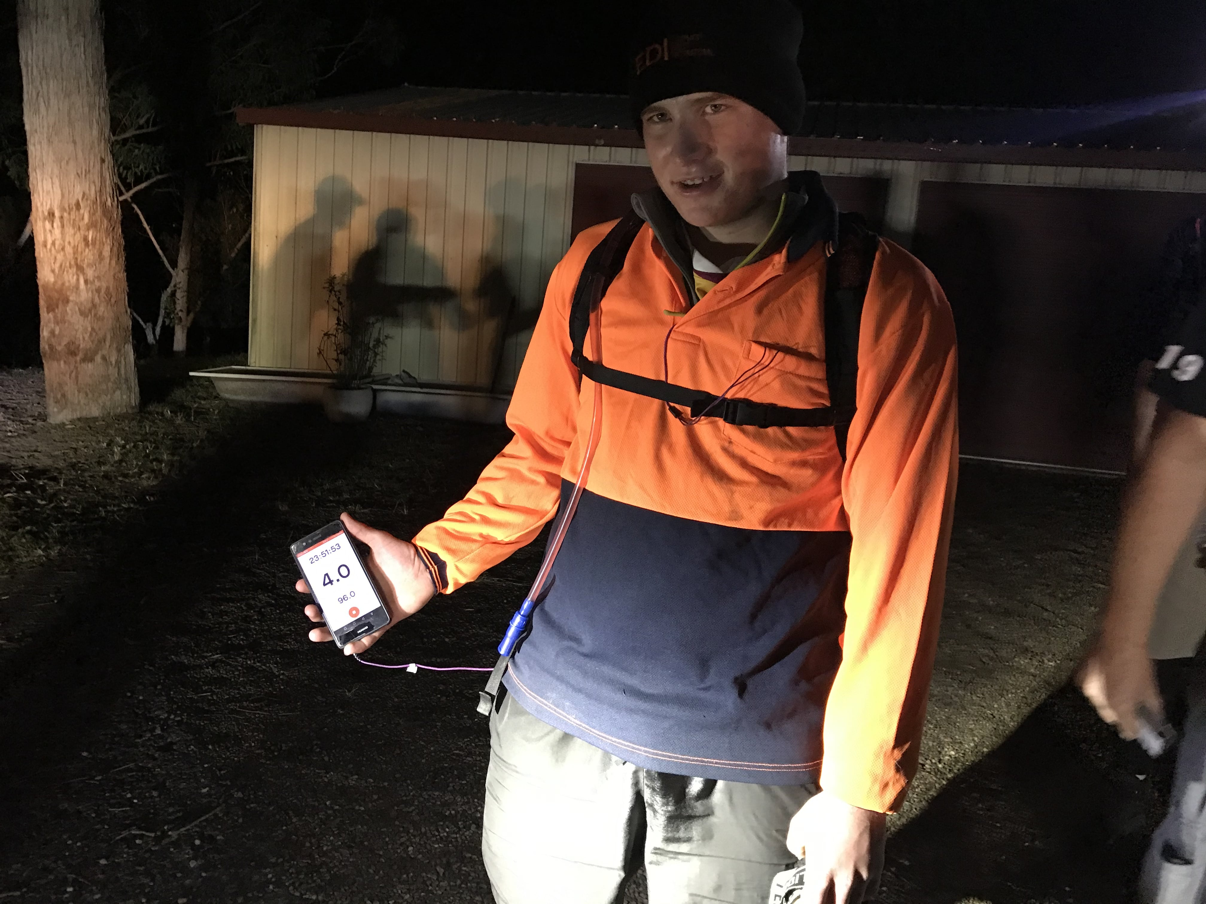 Sam Barham holding up his phone showing the Strava app which indicates he has walked 96kms under 24 hours
