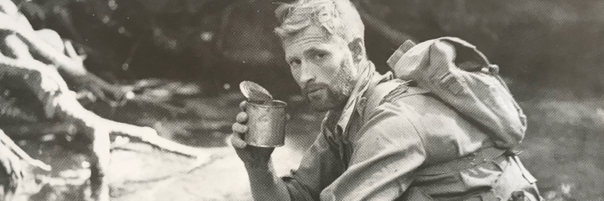 An old photograph of a man drinking from a can during the Kokoda Campaign battle