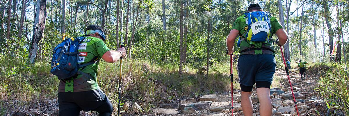 Two men walking up a hill in the Australian bush wearing hiking attire