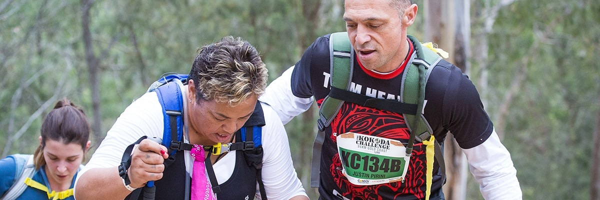 Man helping woman hike up a hill during the Kokoda Challenge event