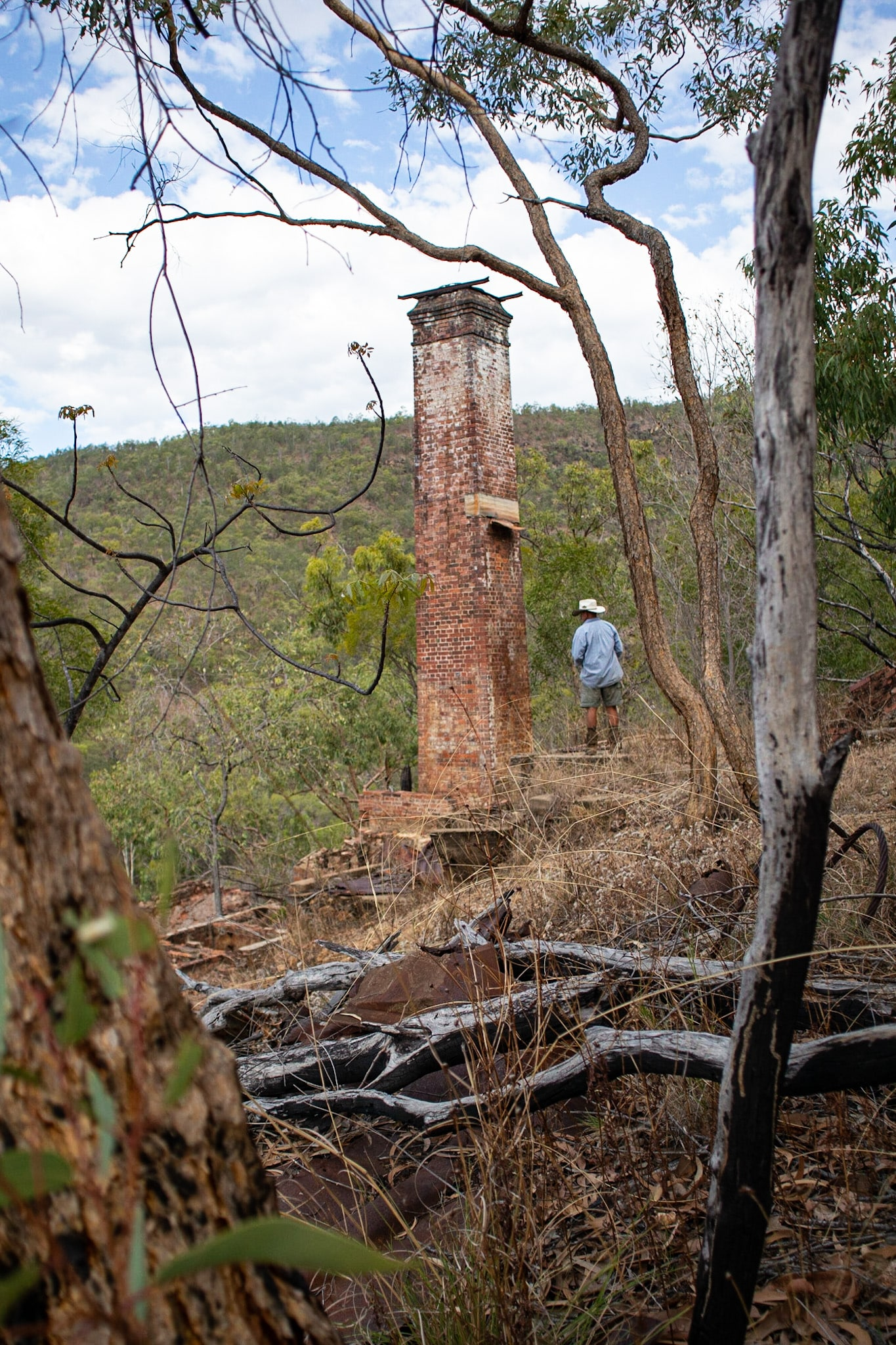 Man in cowboy attire standing in front of an old abandoned chimney in a mining town in the Australian bush