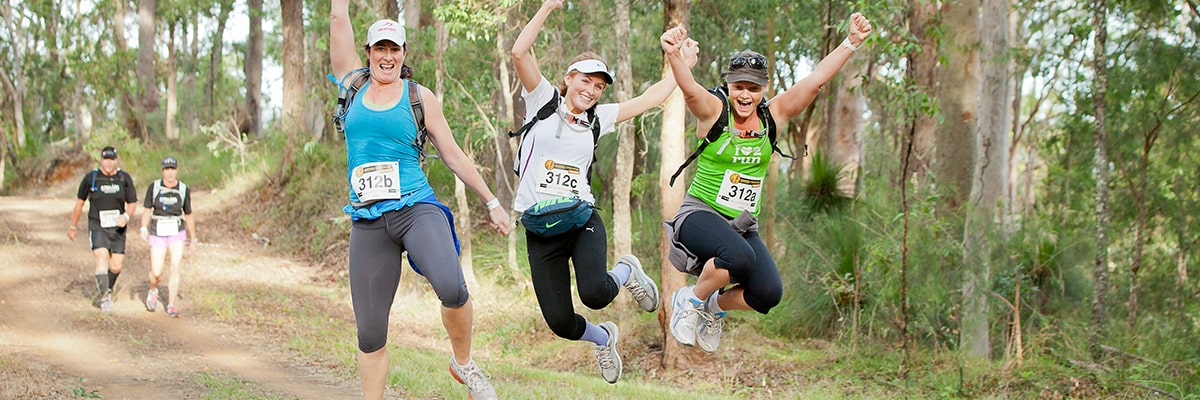 Three ladies leaping in the air while they complete an adventure race the Kokoda Challenge