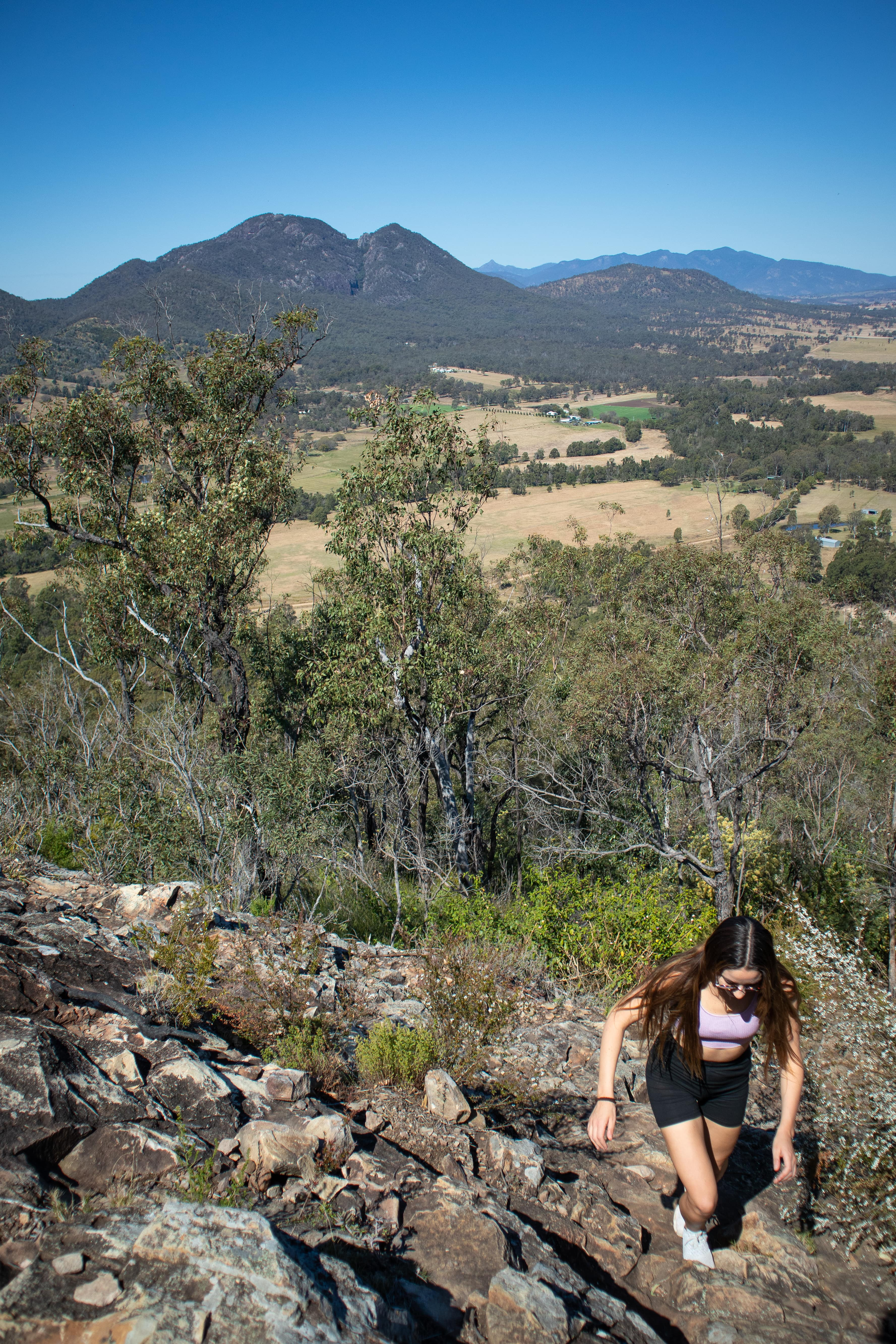 girl climbing up a steep rocky incline with mountainous views of the scenic rim behind her
