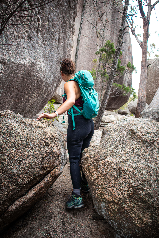 Girl wearing a backback hiking between two rocks in Girraween National Park