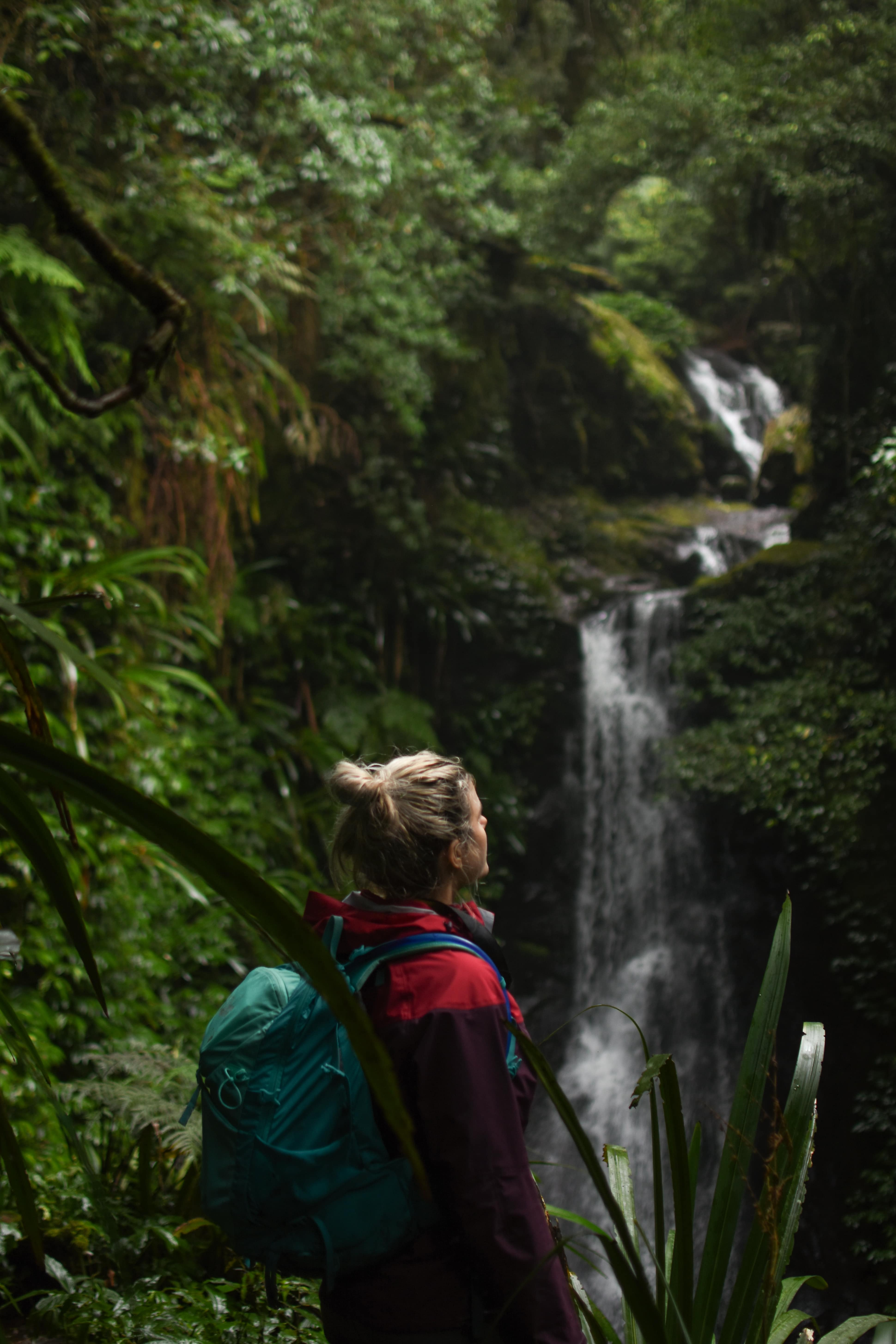 Girl looking out at waterfall on a wet, foggy day in a rainforest