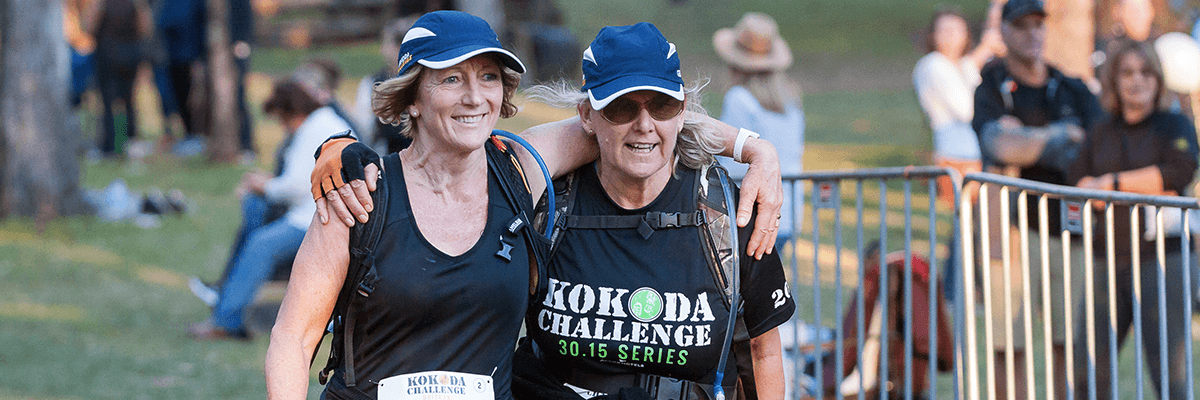 Two ladies arm in arm crossing the finish line at the Kokoda Challenge event